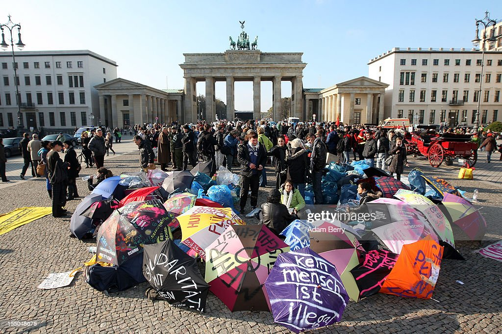 Umbrellas, including one with the words 'Kein Mensch Ist Illegal,' or 'No One Is Illegal,' cover the belongings of protesting refugees in front of the Brandenburg Gate on the seventh day of their hunger strike on October 31, 2012 in Berlin, Germany. The demonstrators, predominantly from Iran, Afghanistan and Iraq, are subsisting on only water, tea and coffee without sugar, and despite the cold temperatures are have been forbidden by the police to have blankets, tents, or isomattresses, the possession of which would change the official status of the protest, registered in advance, from a 'demonstration' to a 'camp.' They have been sitting in front of the Brandenburg Gate since October 24 and say they will continue their strike until the German government responds to their demands for a halt to deportations and faster processing of asylum applications. Meanwhile the police have been criticized by local party-affiliated as well as non-partisan activist groups for their restrictions.