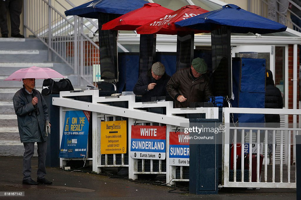 Umbrellas up as rain falls at Lingfield racecourse on March 30, 2016 in Lingfield, England.