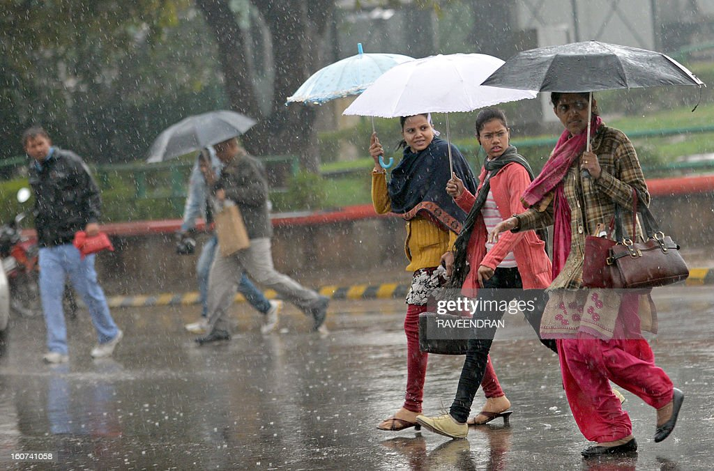 Umbrella-toting pedestrians cross a road as rain falls in New Delhi on February 5, 2013. Heavy rains lashed the Indian capital bringing down the mercury and throwing normal life out of gear.