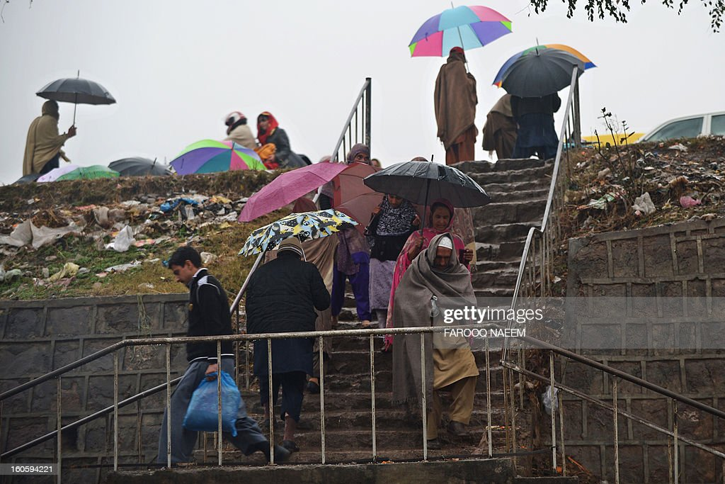 Umbrella-toting pedestrians walk on a flight of stairs during a downpour in Islamabad on February 3, 2013. A strong weather system is expected to generate widespread thunderstorms and rain with snowfall in most parts of the country for the next three to four days, a Pakistan Meteorological Department (PMD) spokesman said. AFP PHOTO/Farooq NAEEM