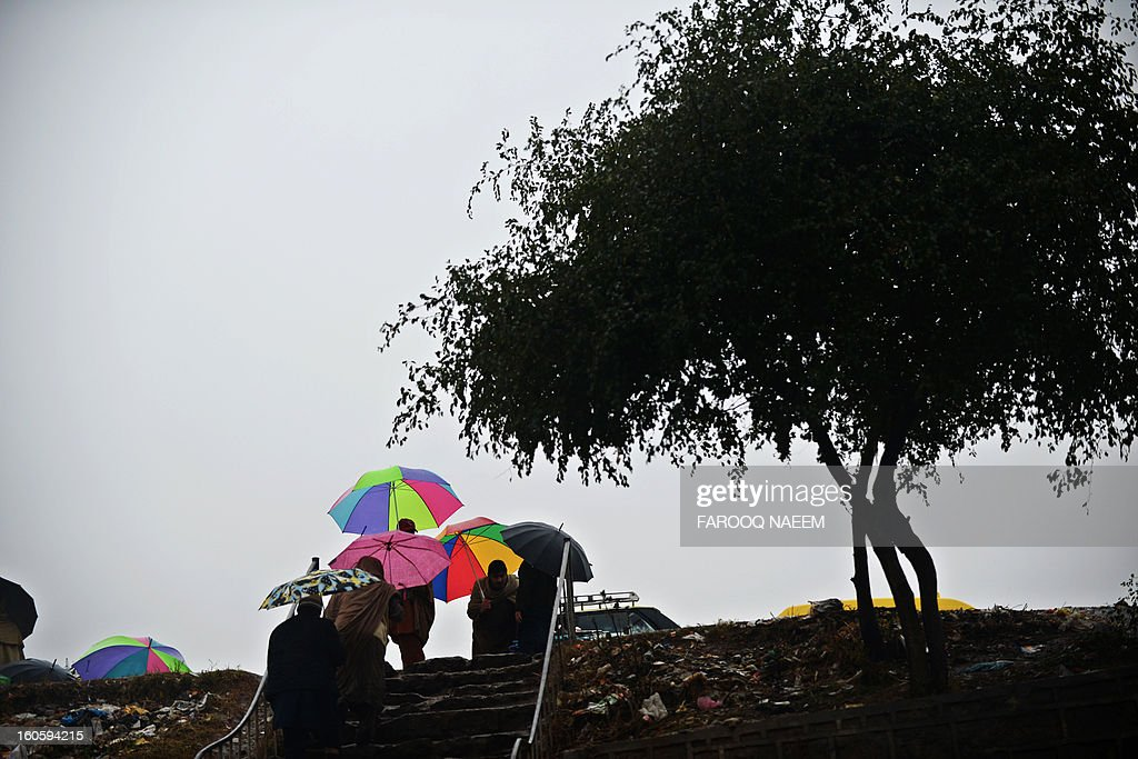 Umbrella-toting pedestrians walk up a flight of stairs during a downpour in Islamabad on February 3, 2013. A strong weather system is expected to generate widespread thunderstorms and rain with snowfall in most parts of the country for the next three to four days, a Pakistan Meteorological Department (PMD) spokesman said. AFP PHOTO/Farooq NAEEM