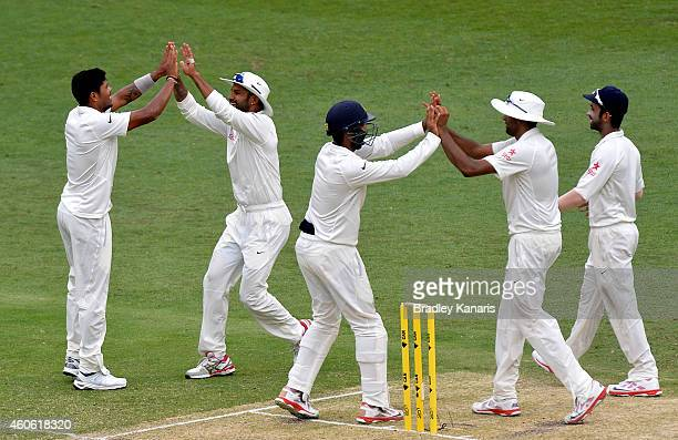 Umesh Yadav of India celebrates with team mates after taking the wicket of Shaun Marsh of Australia during day two of the 2nd Test match between...