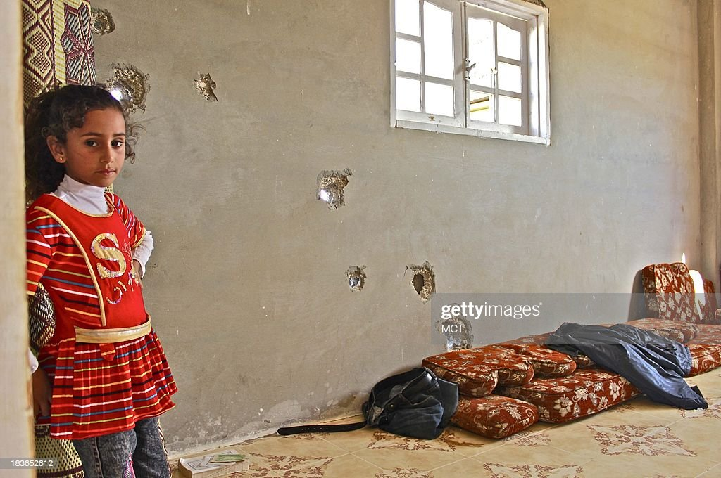 Umm Alaa's daughter stands in a bullet-pocked room as result of tank rounds, adjacent to the room where her grandmother was accidentally killed by security forces last month. According to Umm Alaa, the only witness to the incident, who didn't want to be identified for security reasons, said that random military tank rounds penetrated the wall and struck her mother-in-law in the side of her head.