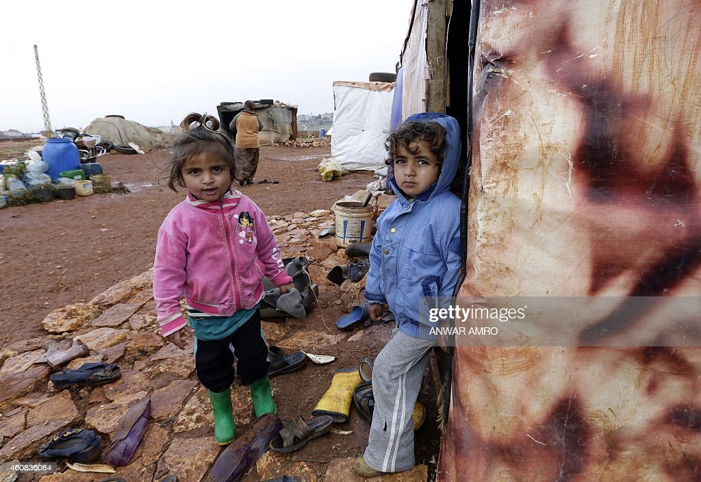 ASSIR Umm Ali's children who fled the violence in the northern Syrian city of Aleppo play at the entrance of their tent at an unofficial refugee camp...