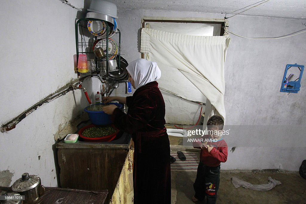 Umm Deeb, a 25-year-old Syrian refugee, cleans olives as her son plays in their house in the northern Lebanese town of Halba on November 20, 2012. Syrian refugees in Lebanon are demanding the creation of a camp like in Turkey and Jordan, but the Lebanese government and the United Nations reject the idea. AFP PHOTO / ANWAR AMRO