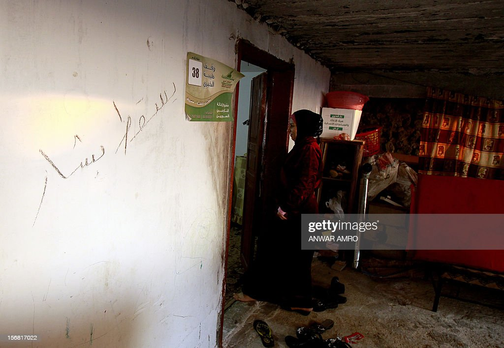 Umm Deeb, a 25-year-old Syrian refugee, enters her house in the northern Lebanese town of Halba on November 20, 2012. Syrian refugees in Lebanon are demanding the creation of a camp like in Turkey and Jordan, but the Lebanese government and the United Nations reject the idea. Arabic writing on wall reads 'Down with (Syrian President) Bashar (al-Assad)'. AFP PHOTO / ANWAR AMRO
