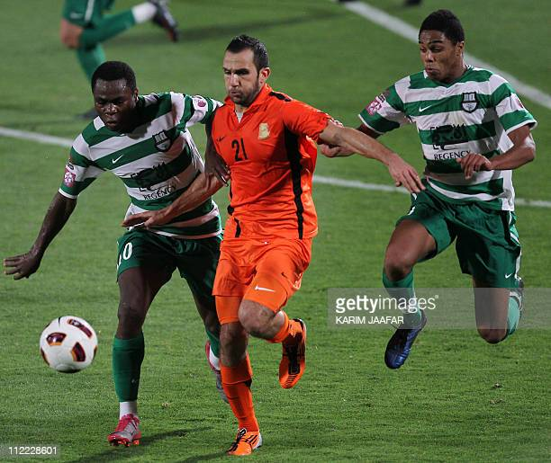 Umm Salal's Moroccan midfielder Adel Ramzi challenges AlAhli's Ghanaian forward Opoku Agyemang and defender Pedro Miguel Correia during their Qatar...