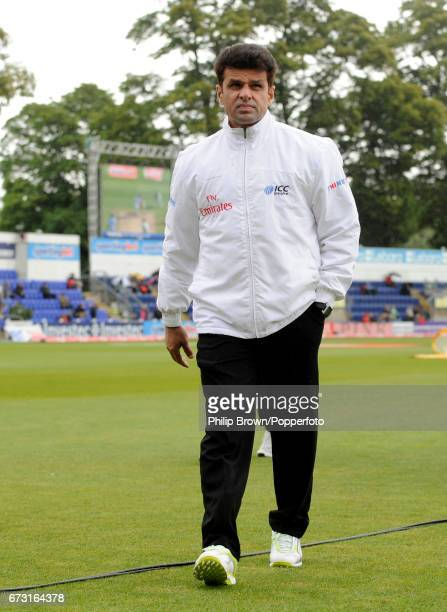 Umpire Aleem Dar leaves the field after inspecting the ground as the start of the 1st Test match between England and Sri Lanka is delayed by rain at...