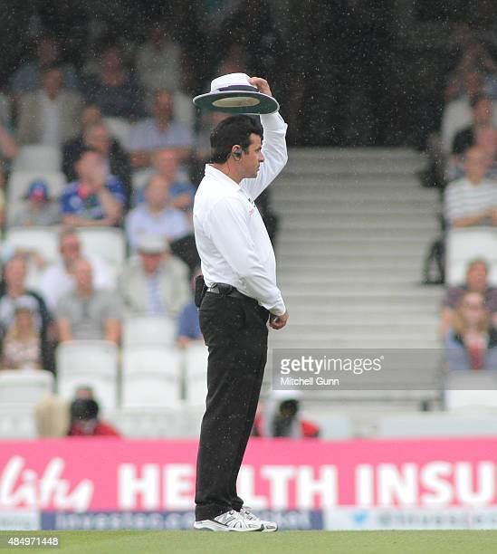Umpire Aleem Dar lifts his hat to check the rain fall during day four of the 5th Investec Ashes Test match between England and Australia at The Kia...