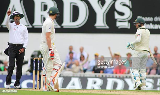 Umpire Aleem Dar signals out as Michael Clarke of Australia walks off after being dismissed during day one of the 5th Investec Ashes Test match...