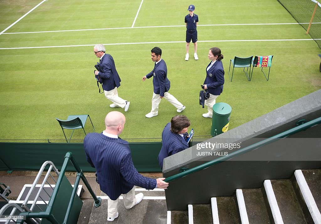 Umpire and line judges arrive on court on the fourth day of the 2016 Wimbledon Championships at The All England Lawn Tennis Club in Wimbledon, southwest London, on June 30, 2016. / AFP / JUSTIN