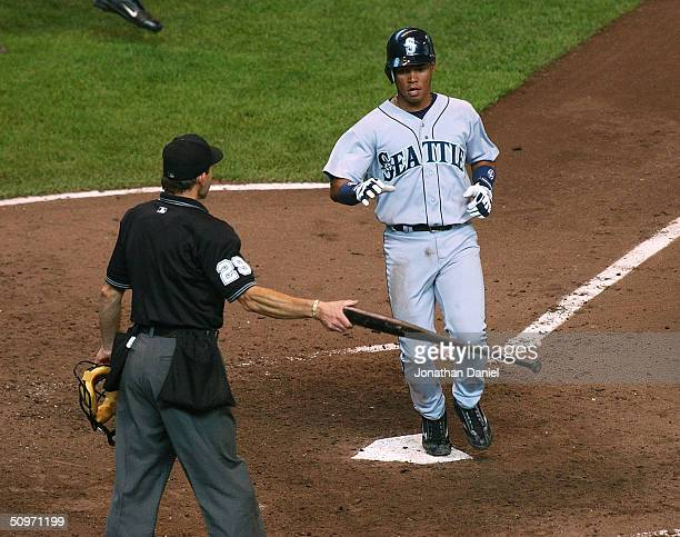 Umpire Bill Hohn hands a bat to Ramon Santiago of the Seattle Mariners as Santiago scores on a single by teammate Jolbert Cabrera in the seventh...