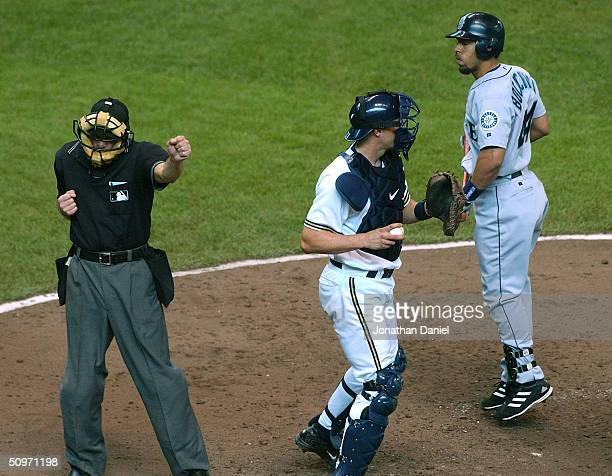 Umpire Bill Hohn rings up Hiram Bocachica of the Seattle Mariners after Bochachica struck out with bases loaded in the sixth inning as Chad Moeller...