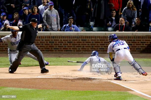 Umpire Bill Welke calls Chris Taylor of the Los Angeles Dodgers safe after sliding into home plate past Willson Contreras of the Chicago Cubs in the...