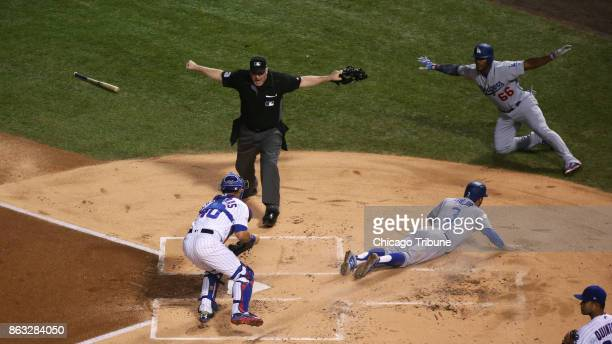 Umpire Bill Welke calls the Los Angeles Dodgers' Chris Taylor safe at home on a double by Cody Bellinger in the first inning against the Chicago Cubs...