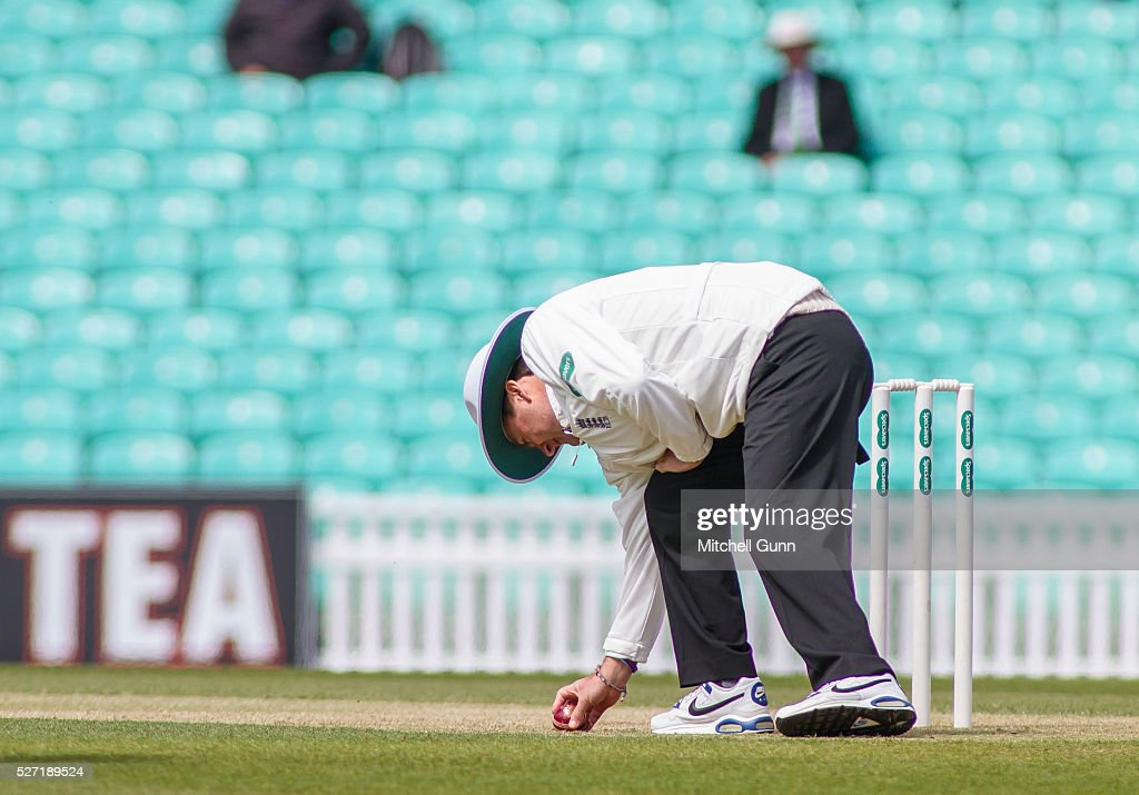 Umpire Billy Taylor rubs a replacement ball onto the batting surface during the Specsavers County Championship Division One match between Surrey and Durham at the Kia Oval Cricket Ground, on May 02, 2016 in London, England.
