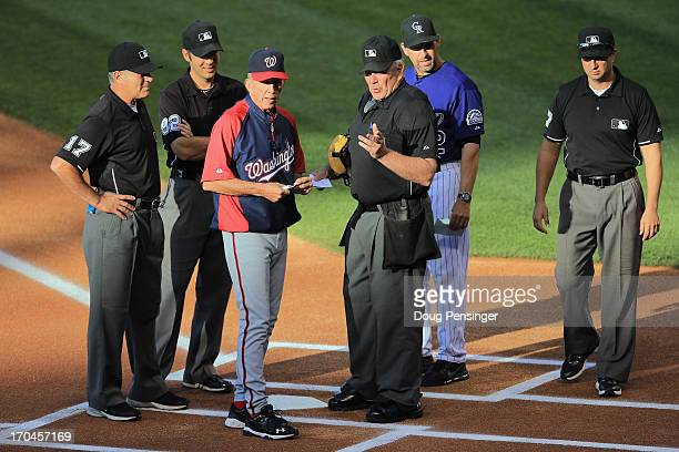 Umpire Bob Davidson reviews the ground rules with manager Davey Johnson of the Washington Nationals as umpires John Hirschbeck James Hoye Jim...
