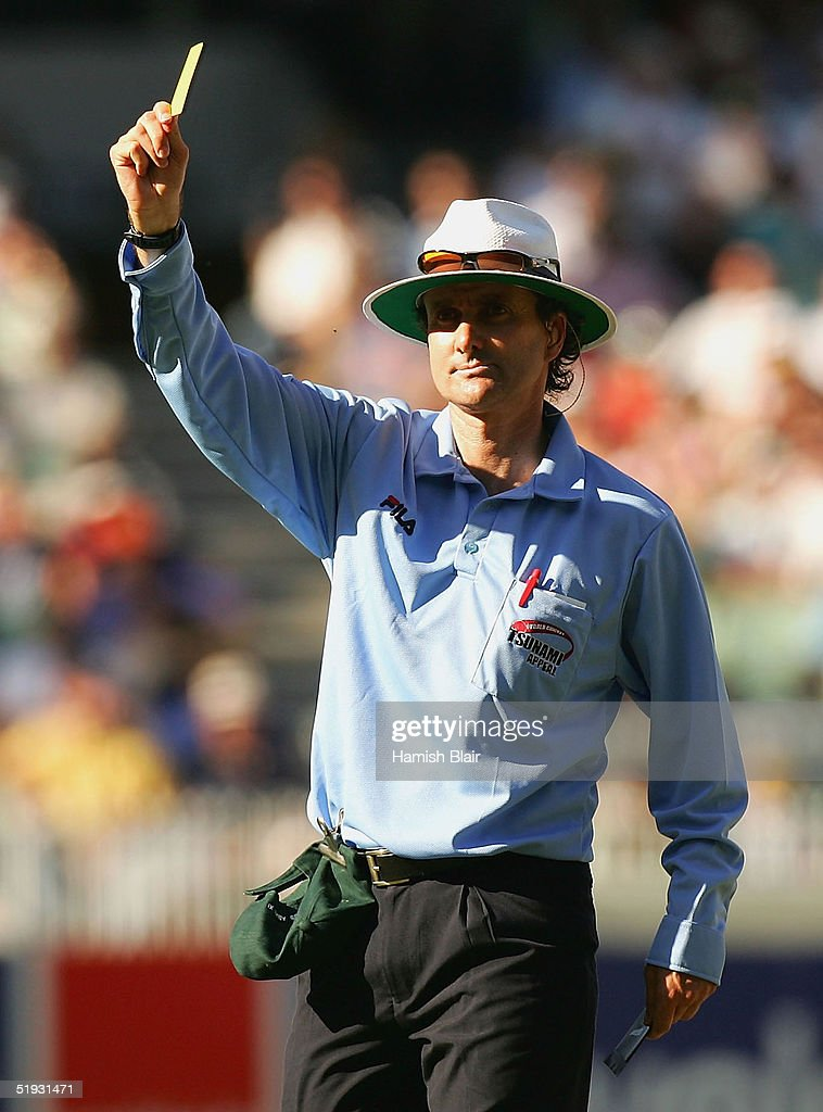 Umpire Brent Bowden shows a yellow card after Shane Warne of the Rest of the World XI left the field without being dismissed as part of a bet to...