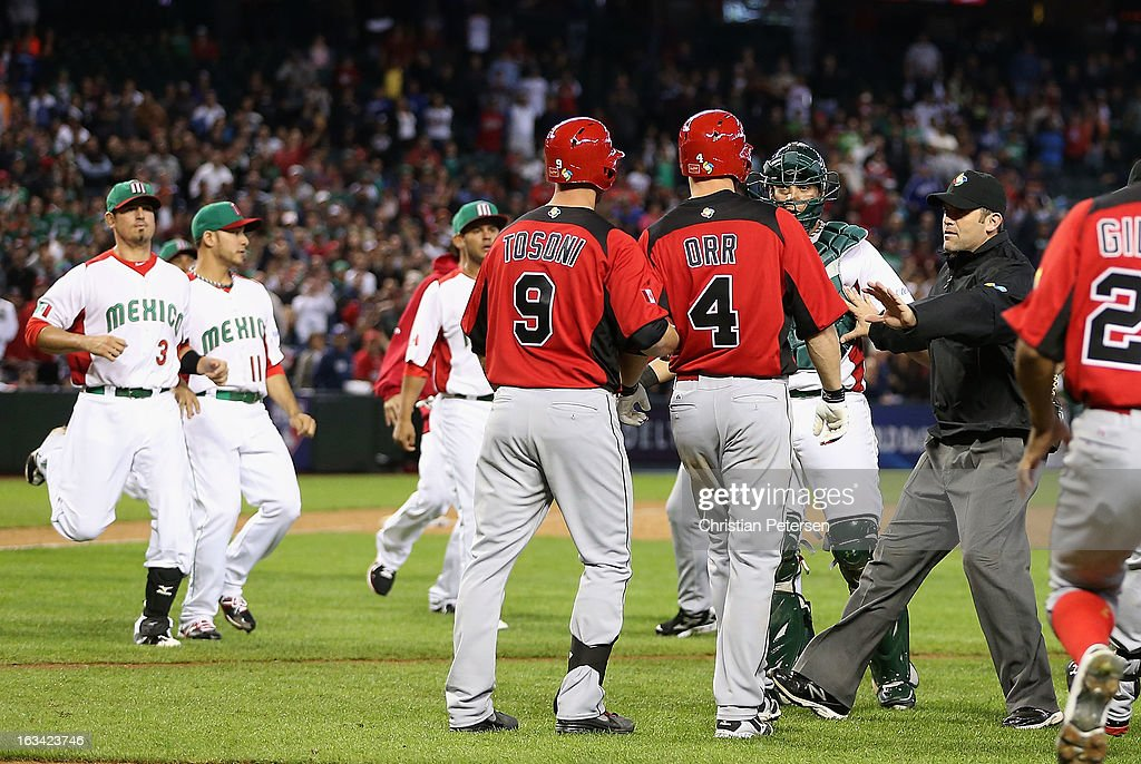 Umpire Brian Knight attempts to seperate Pete Orr and Rene Tosoni of Canada from catcher Sebastian Valle of Mexico of Canada as both teams run onto...