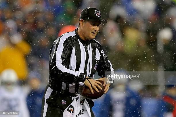 Umpire Carl Paganelli holds a ball on the field after a play during the 2015 AFC Championship Game between the New England Patriots and the...