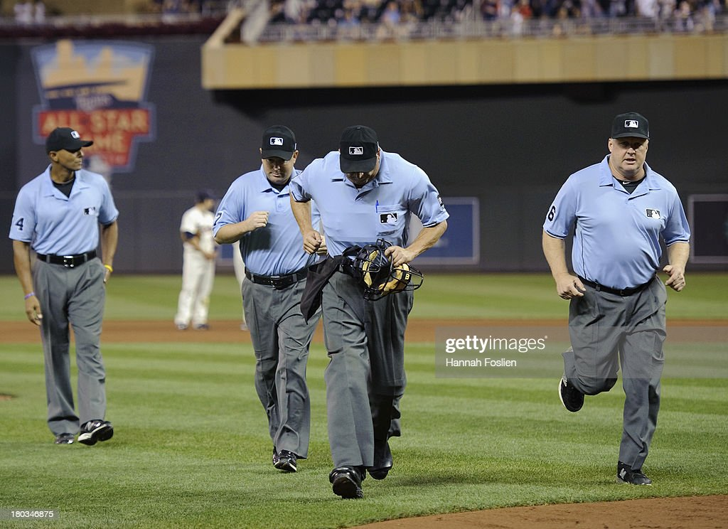 Umpire CB Bucknor #54 stays on the field as umpires Todd Tichenor #97, <a gi-track='captionPersonalityLinkClicked' href=/galleries/search?phrase=Dale+Scott&family=editorial&specificpeople=243427 ng-click='$event.stopPropagation()'>Dale Scott</a> #5 and Bill Miller #26 leave the field to review a ball hit by Josh Reddick #16 of the Oakland Athletics that was ruled a home run during the fifth inning of the game against the Minnesota Twins on September 11, 2013 at Target Field in Minneapolis, Minnesota. The umpires overturned the initial call and gave Reddick a double.