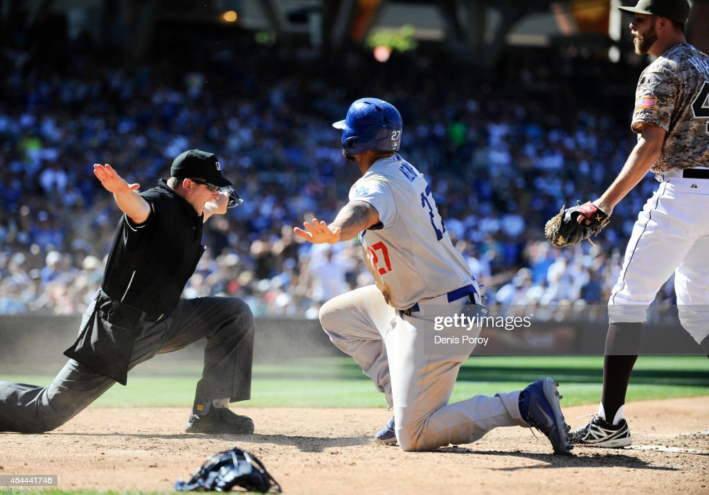 Umpire Clint Fagan signals safe after <a gi-track='captionPersonalityLinkClicked' href=/galleries/search?phrase=Matt+Kemp&family=editorial&specificpeople=567161 ng-click='$event.stopPropagation()'>Matt Kemp</a> #27 of the Los Angeles Dodgers scored ahead of the tag of <a gi-track='captionPersonalityLinkClicked' href=/galleries/search?phrase=Jesse+Hahn&family=editorial&specificpeople=12495165 ng-click='$event.stopPropagation()'>Jesse Hahn</a> #45 of the San Diego Padres during the eighth inning of a baseball game at Petco Park August, 31, 2014 in San Diego, California.