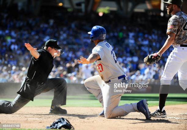 Umpire Clint Fagan signals safe after Matt Kemp of the Los Angeles Dodgers scored ahead of the tag of Jesse Hahn of the San Diego Padres during the...