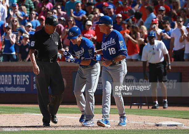 Umpire Dale Scott listens to Chris Getz and Rusty Kuntz first base coach of the Kansas City Royals appeal on a called out on Getz at first base that...