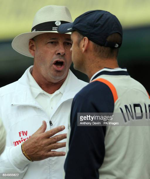 Umpire Daryl Harper speaks with India coach Gary Kirsten as the players leave the field for bad light immediately after walking out for England's...