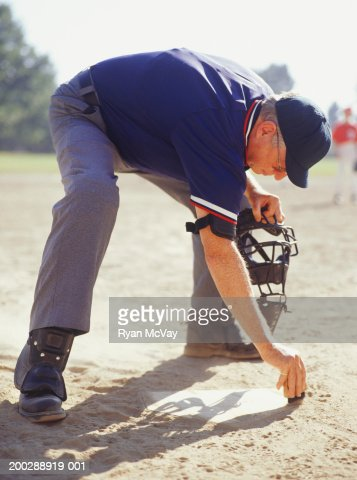 Umpire dusting off plate in baseball stadium