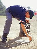 Umpire dusting off plate in baseball stadium