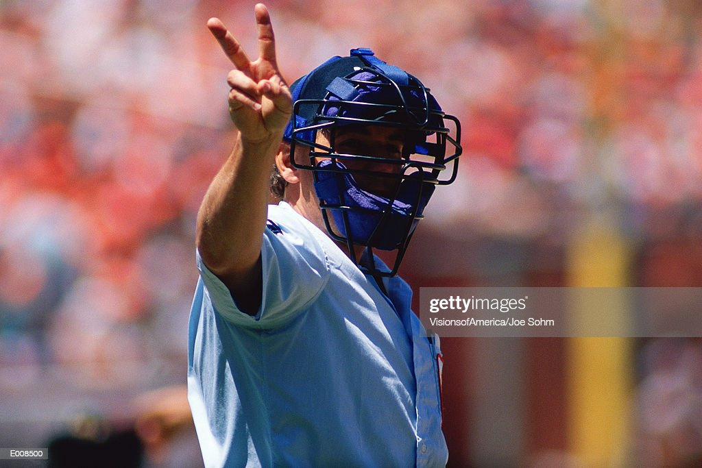 Umpire holding up signal with hand