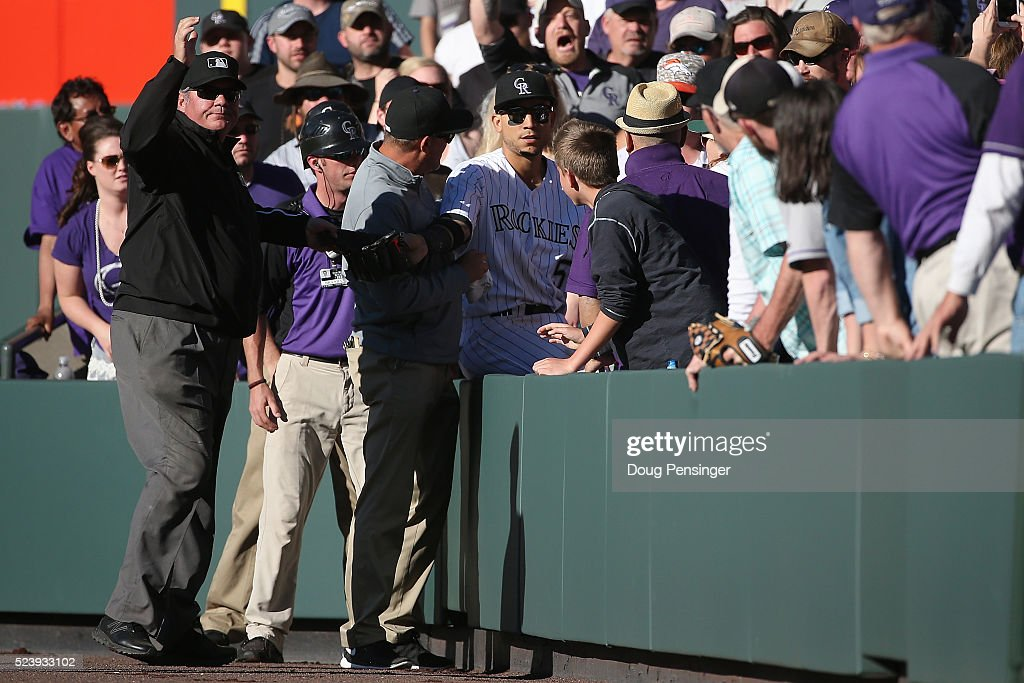 Umpire <a gi-track='captionPersonalityLinkClicked' href=/galleries/search?phrase=Hunter+Wendelstedt&family=editorial&specificpeople=171442 ng-click='$event.stopPropagation()'>Hunter Wendelstedt</a> calls an out that would be overturned by video review after rightfielder Carlos Gonzalez #5 of the Colorado Rockies dives into the stands on a foul ball by Yasmani Grandal #9 of the Los Angeles Dodgers in the ninth inning at Coors Field on April 24, 2016 in Denver, Colorado. The Dodgers defeated the Rockies 12-10.