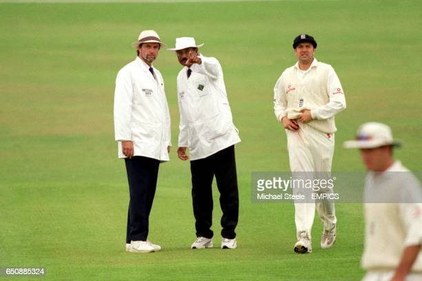 Umpire Javed Akhtar discusses a point with fellow umpire Peter Willey