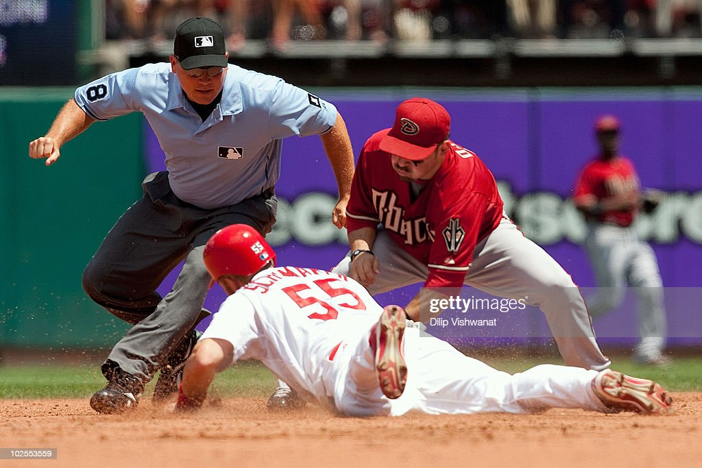 Umpire Jeff Kellogg looks to make a call as Skip Schumaker of the St Louis Cardinals slides back to second base against Augie Ojeda of the Arizona...