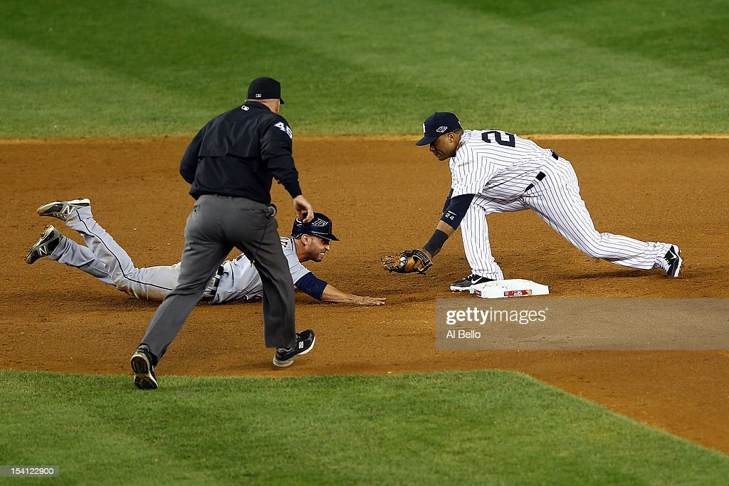 Umpire Jeff Nelson calls <a gi-track='captionPersonalityLinkClicked' href=/galleries/search?phrase=Omar+Infante&family=editorial&specificpeople=203255 ng-click='$event.stopPropagation()'>Omar Infante</a> #4 of the Detroit Tigers safe as he dove back into second base against <a gi-track='captionPersonalityLinkClicked' href=/galleries/search?phrase=Robinson+Cano&family=editorial&specificpeople=538362 ng-click='$event.stopPropagation()'>Robinson Cano</a> #24 of the New York Yankees in the top of the eighth inning during Game Two of the American League Championship Series at Yankee Stadium on October 14, 2012 in the Bronx borough of New York City.