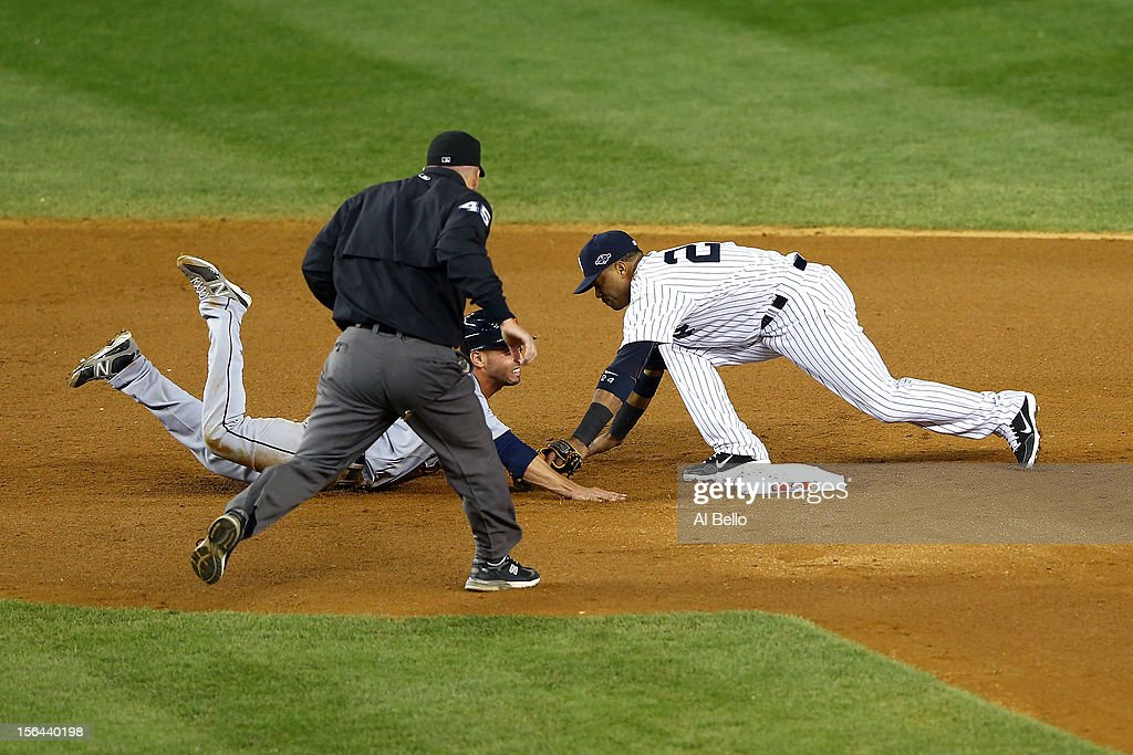 Umpire Jeff Nelson calls Omar Infante #4 of the Detroit Tigers safe as he dove back into second base against Robinson Cano #24 of the New York Yankees in the top of the eighth inning during Game Two of the American League Championship Series at Yankee Stadium on October 14, 2012 in the Bronx borough of New York City.
