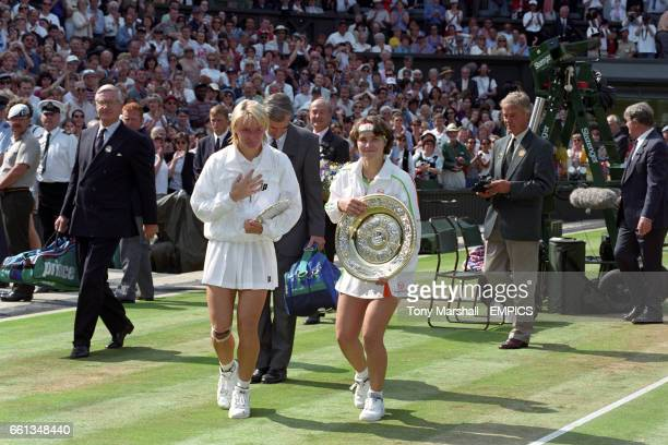 Umpire Jeremy Shales looks on as Martina Hingis and Jana Novotna make their way off the court after Hingis's victory