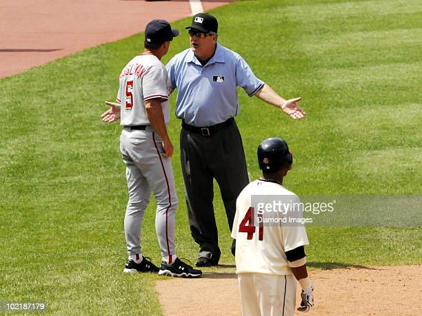 Umpire Jerry Crawford discusses a play with manager Jim Riggleman of the Washington Nationals as catcher Carlos Santana of the Cleveland Indians...