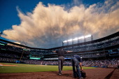 Umpire Jerry Layne upholds a safe call on a challenged play on a run scored by Troy Tulowitzki of the Colorado Rockies as clouds fill the sky over...