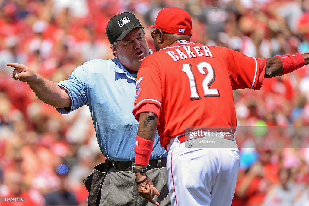 Umpire Joe West argues a call with Manager Dusty Baker #12 of the Cincinnati Reds during a game against the San Diego Padres at Great American Ball Park on August 11, 2013 in Cincinnati, Ohio.