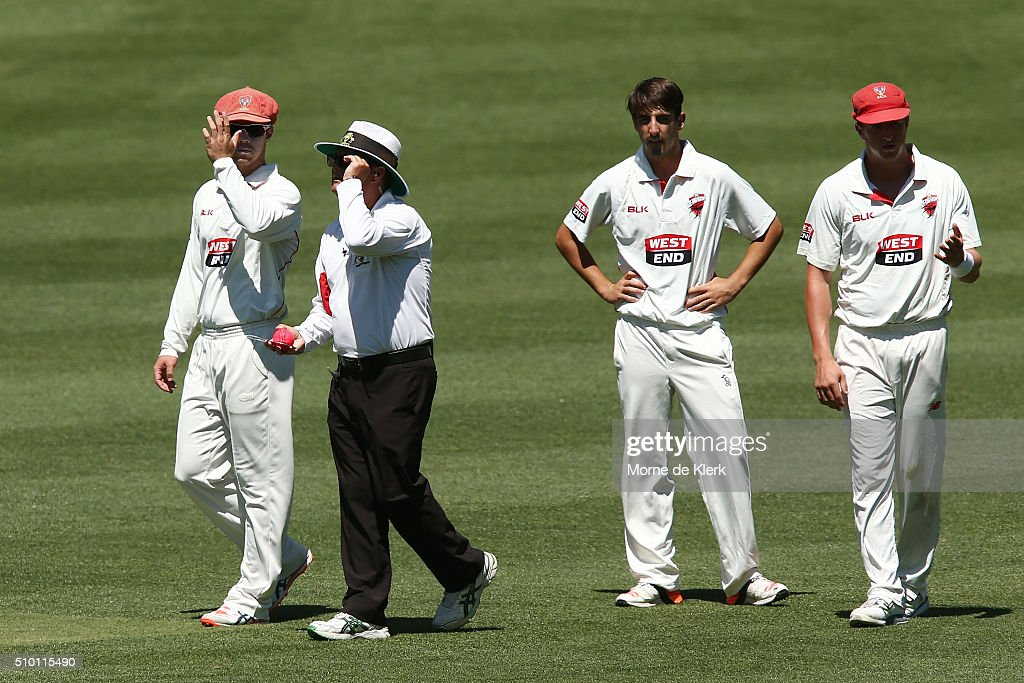 Umpire John Ward discusses the state of the pink match ball with Redbacks players during day one of the Sheffield Shield match between South Australia and Victoria at Adelaide Oval on February 14, 2016 in Adelaide, Australia.