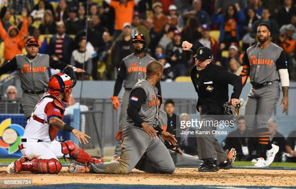 Umpire Lance Barksdale calls Jonathan Schoop of the Netherlands out at home after he was tagged by catcher Yadier Molina of the Puerto Rico in the...