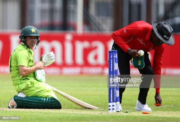 Umpire Langton Rusere picks up the bails as Bibi Nahida of Pakistan kneels on the turf after being run out by Marizanne Kapp of South Africa during...
