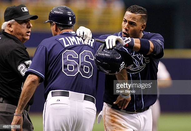 Umpire Larry Vanover and third base coach Tom Foley of the Tampa Bay Rays attempts to hold back Yunel Escobar of the Tampa Bay Rays as he argues with...