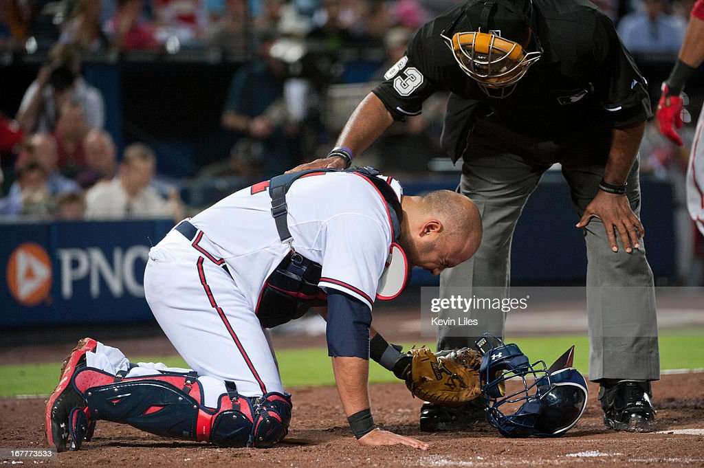 Umpire Laz Diaz puts his hand on Gerald Laird of the Atlanta Braves after Laird was hit with a pitch during the sixth inning at Turner Field on April...