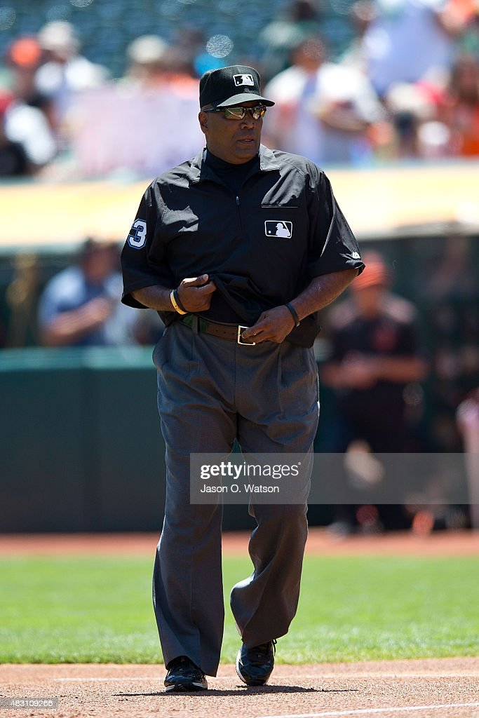 MLB umpire Laz Diaz stands on the field before the game between the Oakland Athletics and the Baltimore Orioles at Oco Coliseum on August 5 2015 in...