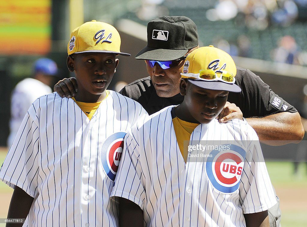 Umpire Laz Diaz talks with two young players of the Jackie Robinson West USA Little League Champions from Chicago who were honored before the game...