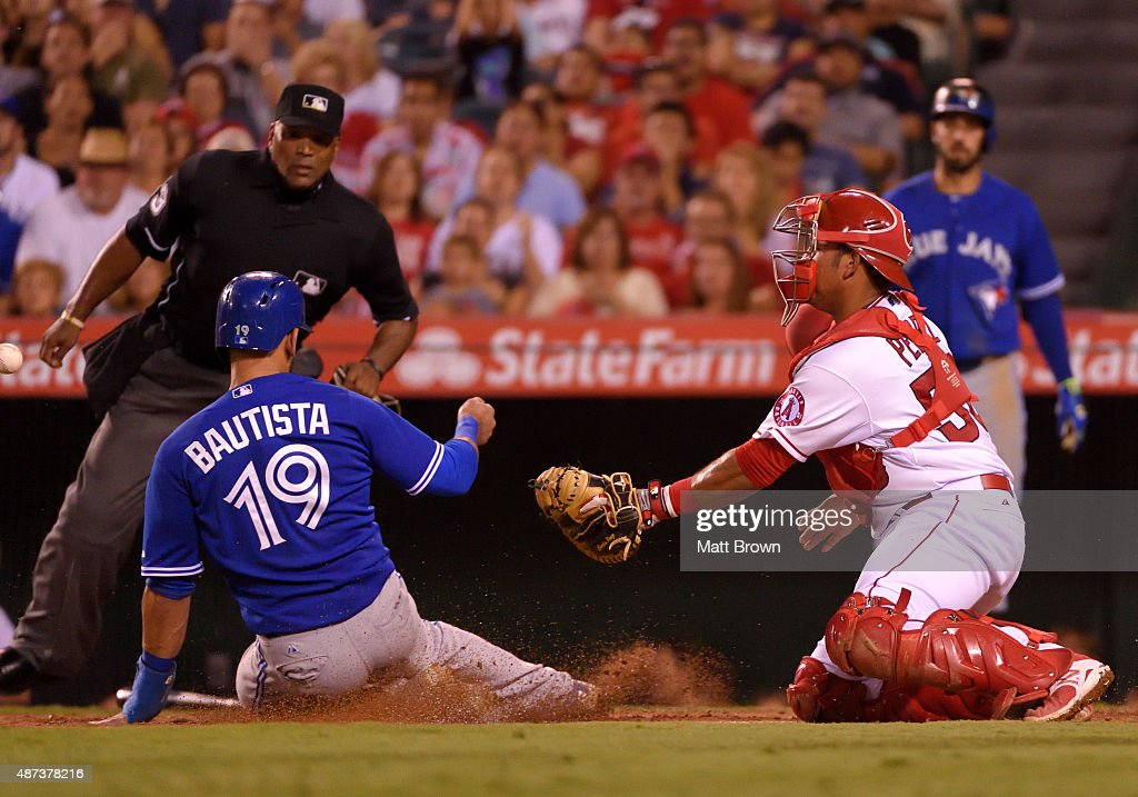 Umpire Laz Diaz watches as Jose Bautista of the Toronto Blue Jays slides to score as Carlos Perez of the Los Angeles Angels of Anaheim attempts to...