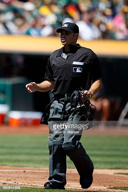 MLB umpire Mark Wegner stands on the field during the third inning between the Oakland Athletics and the Seattle Mariners at the Oakland Coliseum on...